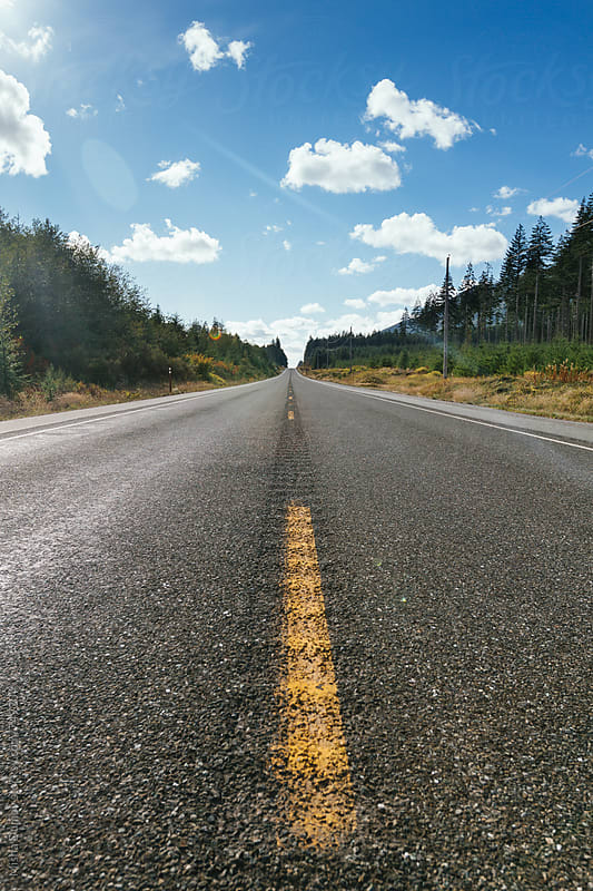 Vertical low angle view of an open road with blue sky and white clouds by Mihael Blikshteyn for Stocksy United