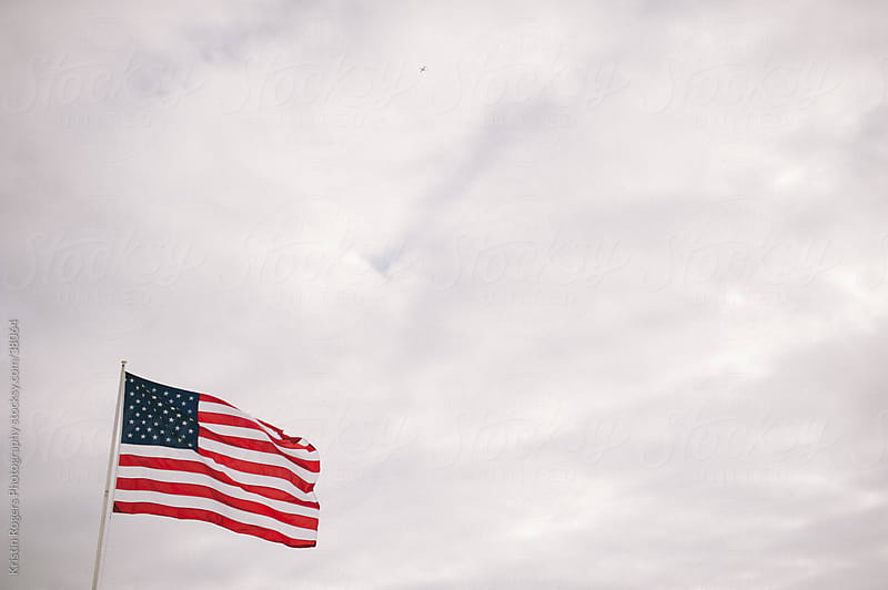 American Flag blowing in a cloudy sky by Kristin Rogers Photography for Stocksy United