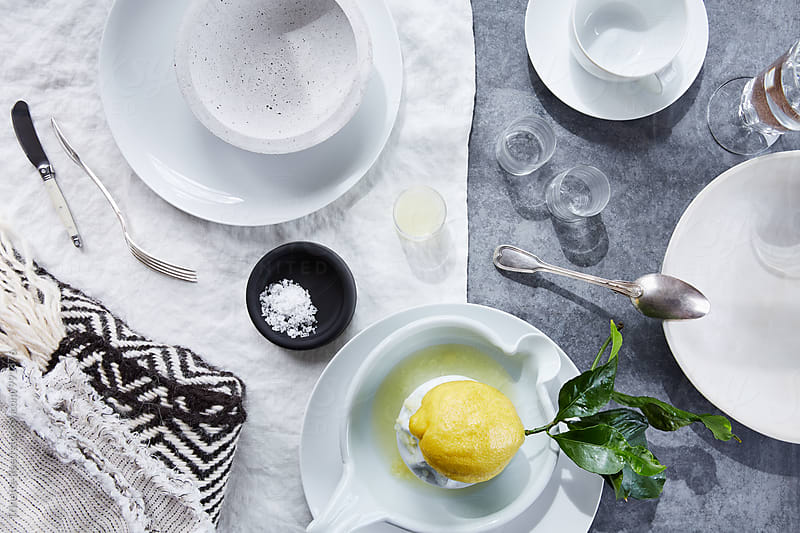 Fresh squeezed lemon juice with salt and dinnerware by Trinette Reed for Stocksy United