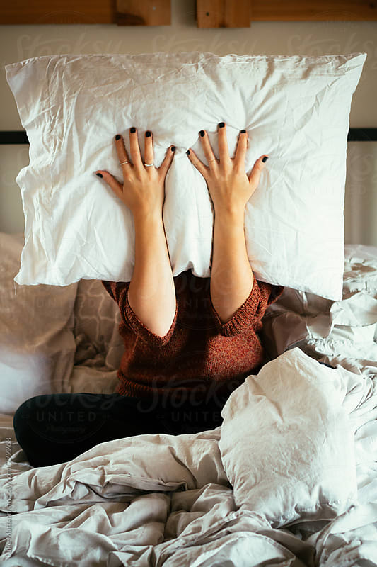 Young Woman Holding Pillow In Front Of Face On Bed by Luke Mattson for Stocksy United