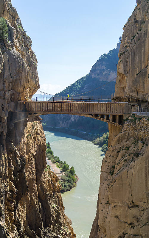 Man walking on the bridge of a canyon in Caminito del Rey by ACALU Studio for Stocksy United