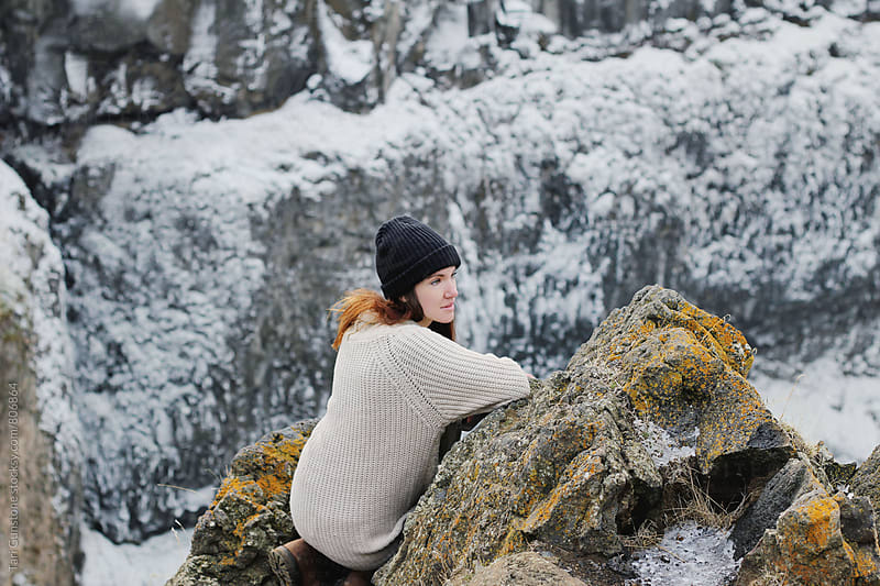 Woman sitting on rock above frozen canyon by Tari Gunstone for Stocksy United