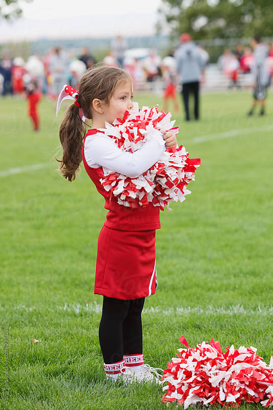 A young cheerleader holds her pom poms and watches the football game by Tana Teel for Stocksy United