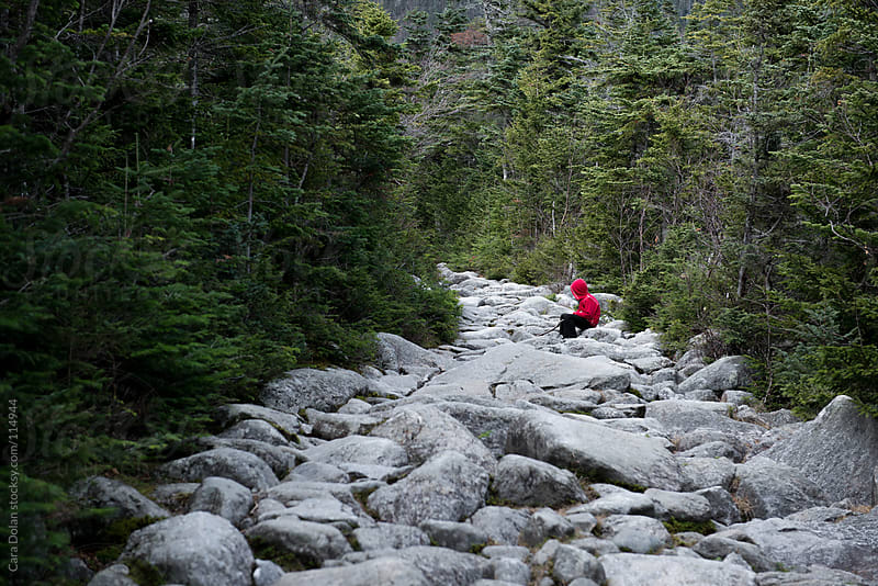 Child wearing red sweatshirt stops to rest along a rocky hiking trail up a mountain by Cara Dolan for Stocksy United