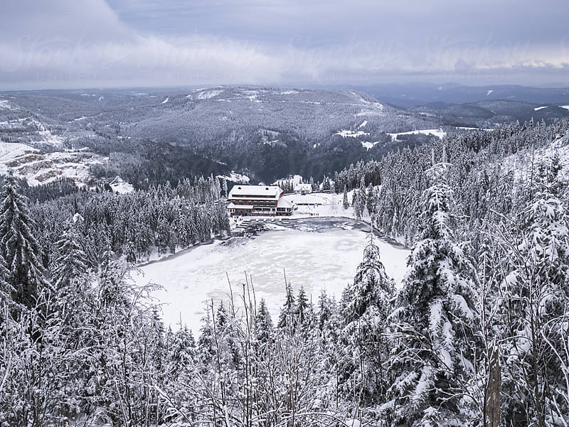 View over the snow covered Mummelsee and Black Forest by Andreas Wonisch for Stocksy United