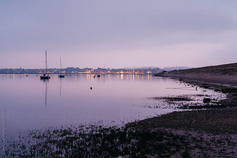 Boats and distant harbour reflected at twilight. Wells-next-the-sea, Norfolk, UK. by Liam Grant for Stocksy United