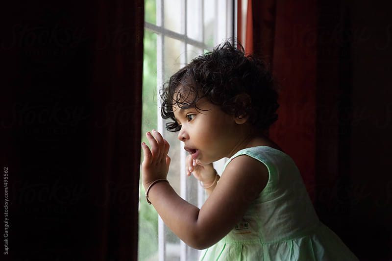 Cute toddler looking out through a glass window in a pensive mood by Saptak Ganguly for Stocksy United