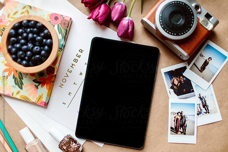 An blank ipad surrounded by a camera & a calendar  by Kristen Curette Hines for Stocksy United