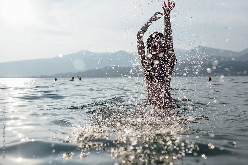 Girl having fun with splashing water by michela ravasio for Stocksy United