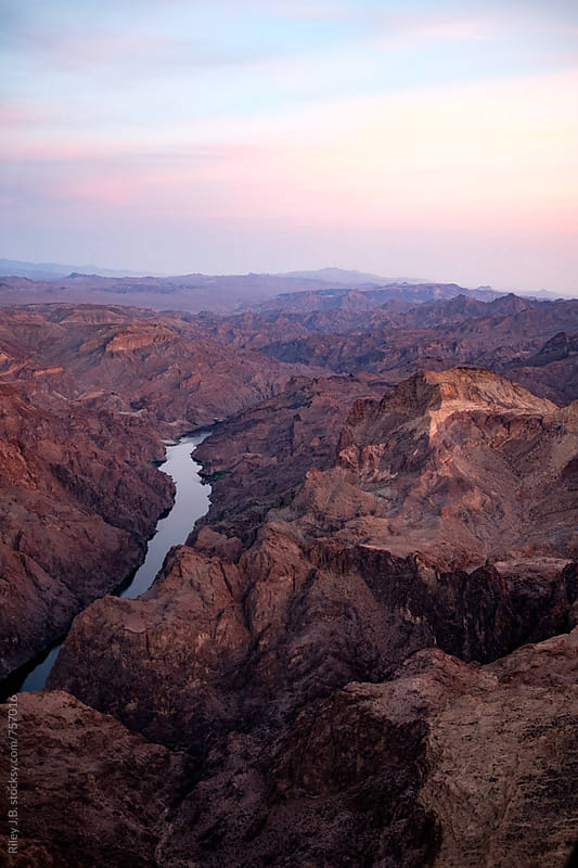 A River Cuts through Desert Mountains at Dusk by Riley Joseph for Stocksy United