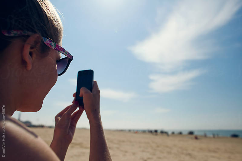 Young woman using her phone on the beach by Denni Van Huis for Stocksy United