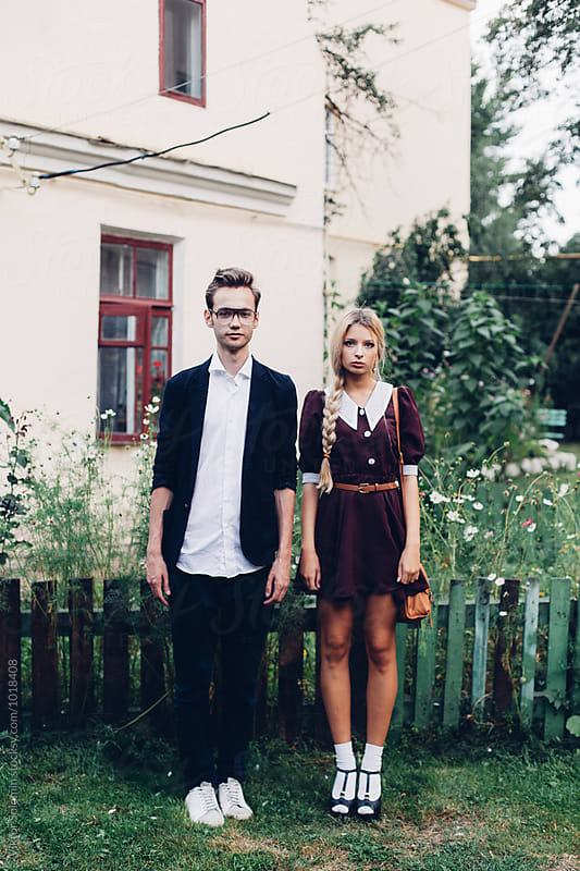 Hipster couple standing straight in the village by Viktor Solomin for Stocksy United