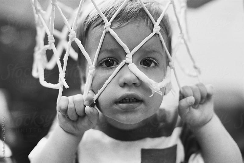 Cute young boy with his head in baskeball net by Jakob for Stocksy United