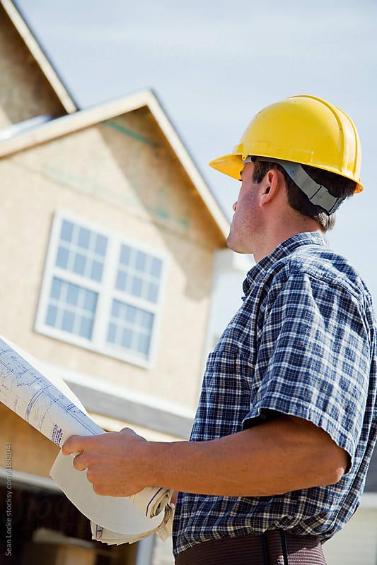 Construction: Builder Checks Plans Against Home by Sean Locke for Stocksy United