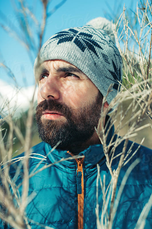 Portrait of a young bearded man wearing winter clothes on a mountain. by BONNINSTUDIO for Stocksy United