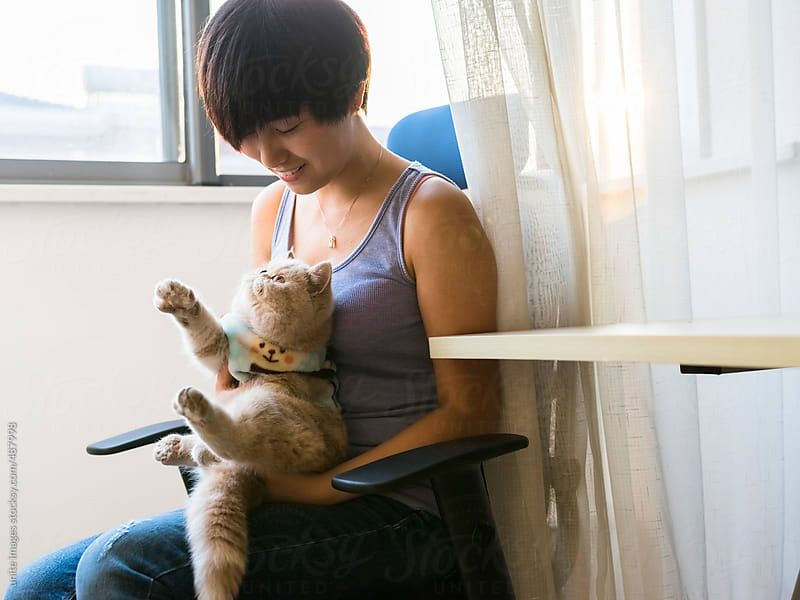 pretty asian girl at home with a cat by unite images for Stocksy United