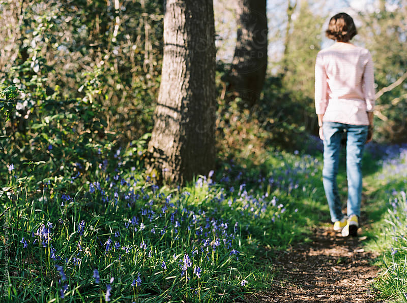 Girl walking on path among bluebells, England by Kirstin Mckee for Stocksy United