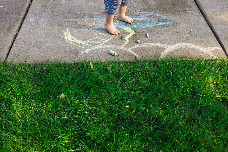 Young boy plays outside with chalk barefoot. by Lucas Saugen for Stocksy United