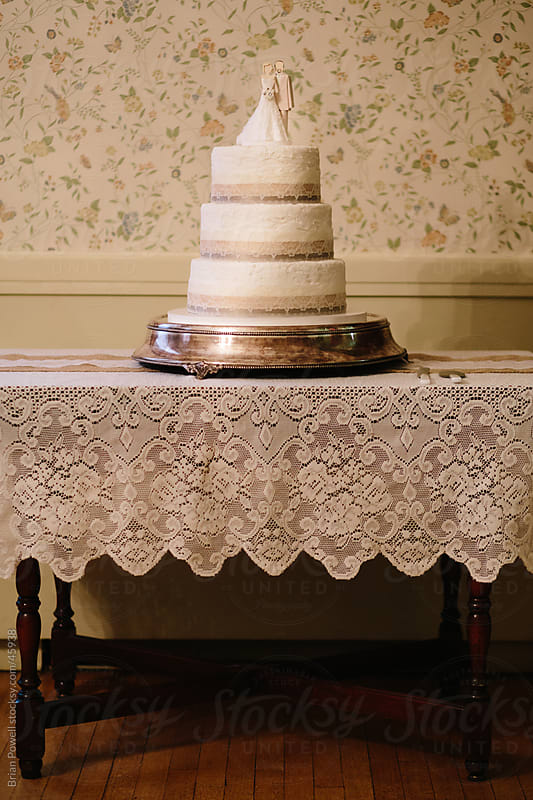 wedding cake on antique table with lace by Brian Powell for Stocksy United