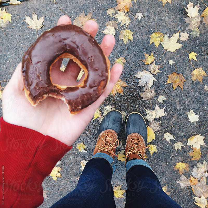 Trendy Girl in Boots in Fall Holding Doughnuts by B. Harvey for Stocksy United