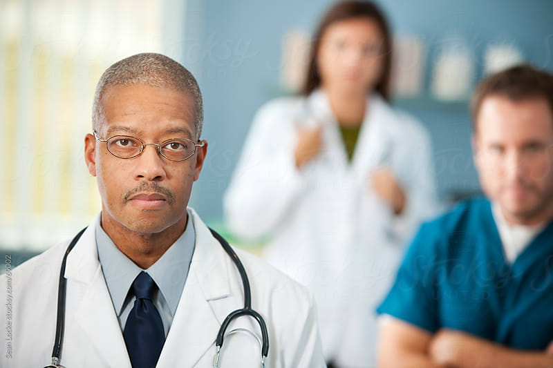 Exam Room: Concerned Male Physician with Team Behind by Sean Locke for Stocksy United