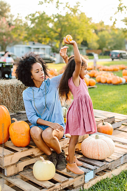 A little girl excited about her pumpkins with her mom by Kristen Curette Hines for Stocksy United