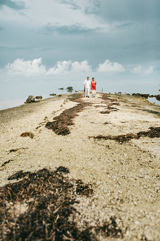 Couple Walking on Jetty by the Ocean by Stephen Morris for Stocksy United