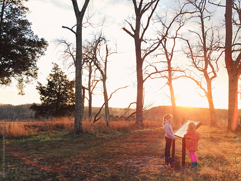 Two girls read a trail map in a field. by Kelsey Gerhard for Stocksy United