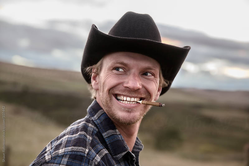 smiling cowboy smoking by Shaun Robinson for Stocksy United