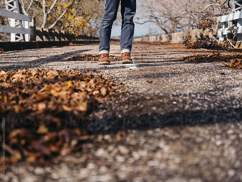 Man wearing jeans and leather boots standing in road covered in fallen leaves. by Jeremy Pawlowski for Stocksy United