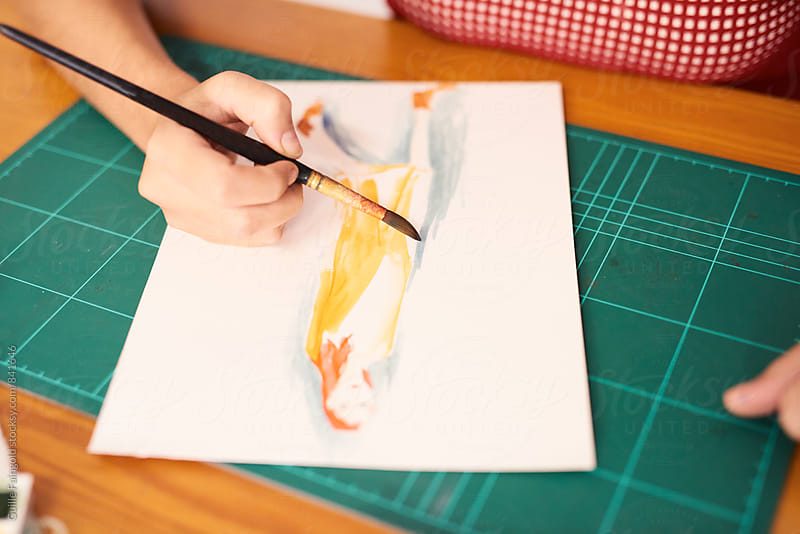 Woman's hands painting with brush and watercolors by Guille Faingold for Stocksy United