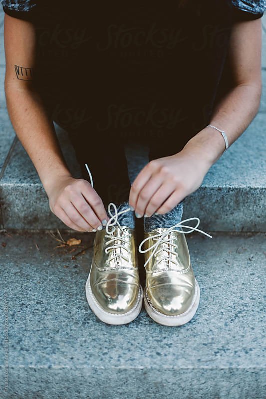 Woman Tying the laces of gold shiny shoes by Treasures & Travels for Stocksy United