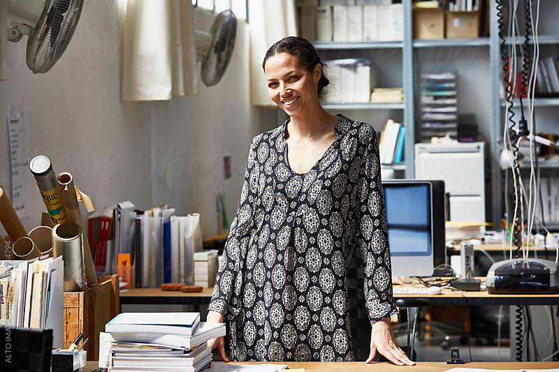 Smiling Businesswoman Standing At Office Desk by ALTO IMAGES for Stocksy United