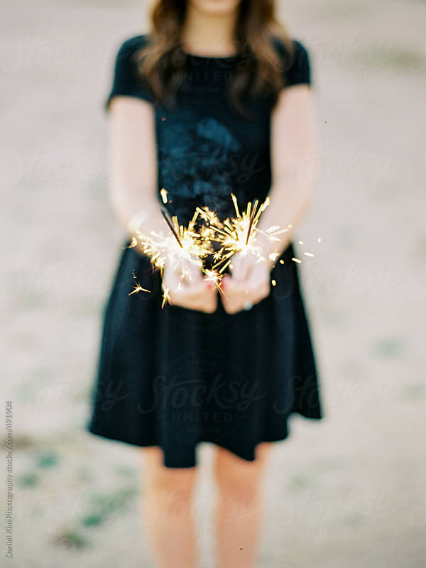 Young woman holding sparklers by Daniel Kim Photography for Stocksy United