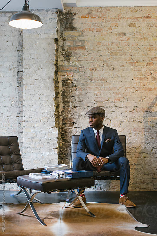 Stylish Young Black Man in Blue Suit Sitting in Upscale Men's Fashion Store by VISUALSPECTRUM for Stocksy United