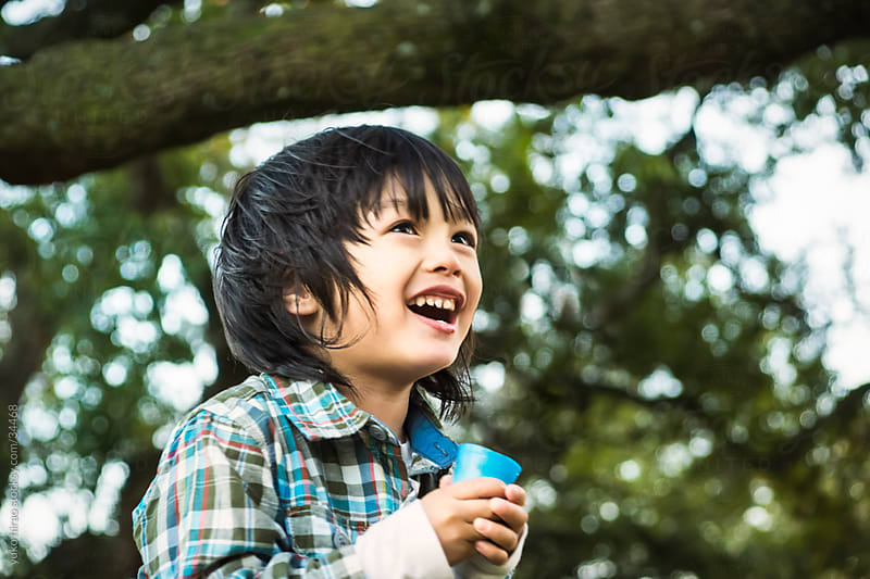 Laughing Asian little boy under trees by yuko hirao for Stocksy United