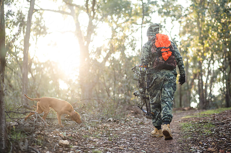 Bow hunter and his dog by Reece McMillan for Stocksy United