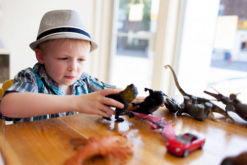 Cute Little Boy Playing with Animal Toys at Coffee Cafe by JP Danko for Stocksy United