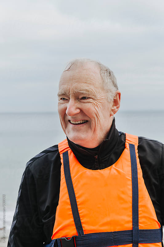 Portrait of senior man in life vest laughing by Lior + Lone for Stocksy United