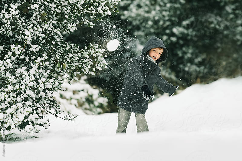 Child throwing snowball by Rebecca Spencer for Stocksy United