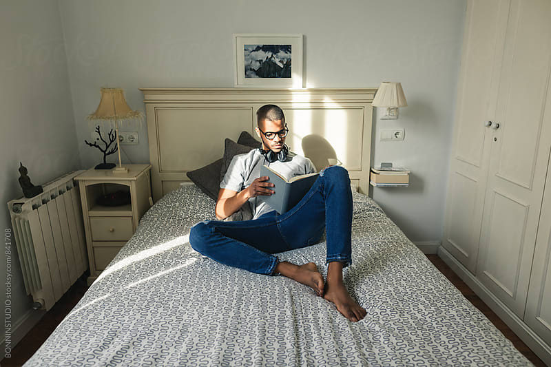 Latin man reading a book in bed. by BONNINSTUDIO for Stocksy United