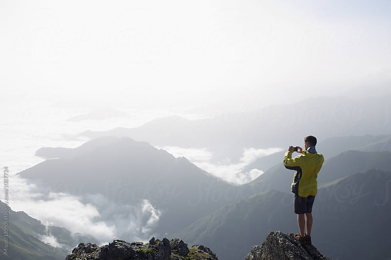 Young man taking a photograph of the scenic view from the top of a mountain by Miquel Llonch for Stocksy United