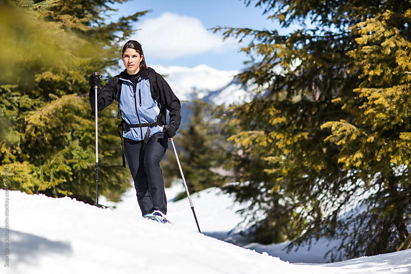 Female snowshoer going snowshoeing on a sunny winter day by Suprijono Suharjoto for Stocksy United