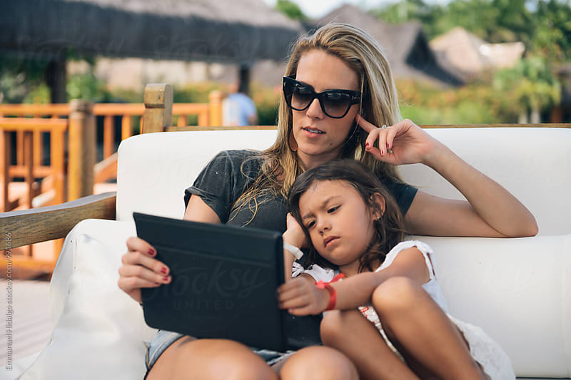 Mother and daughter using a digital tablet while on vacation by Emmanuel Hidalgo for Stocksy United