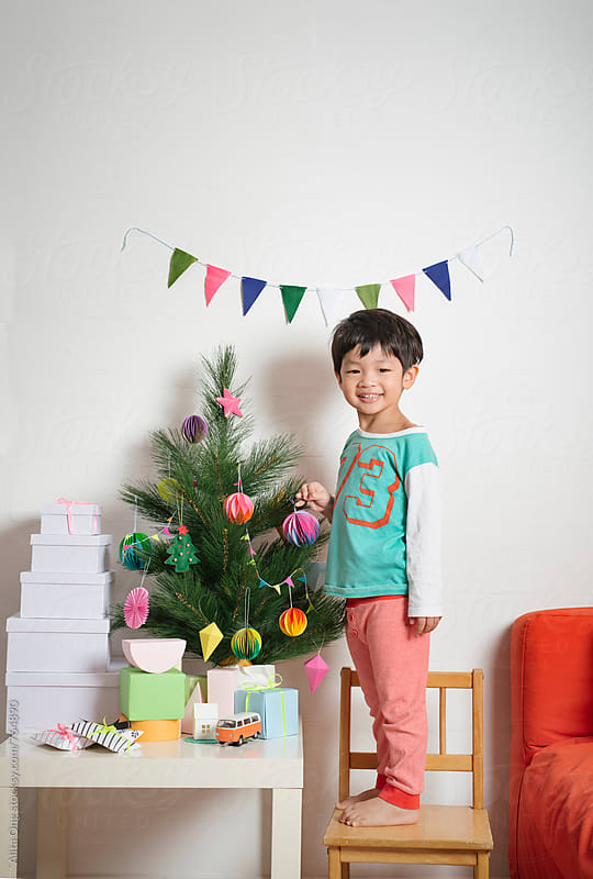 Smiling little boy standing next to holiday tree by Alita Ong for Stocksy United