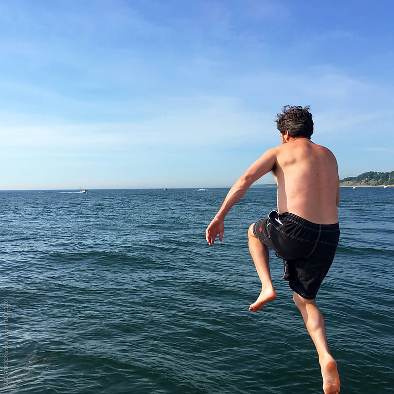 A Man Jumping Into Lake Michigan On A Summer Day by ALICIA BOCK for Stocksy United
