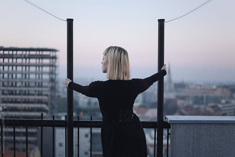 Stylish woman on the roof of the building during sunset from behind by Marija Mandic for Stocksy United
