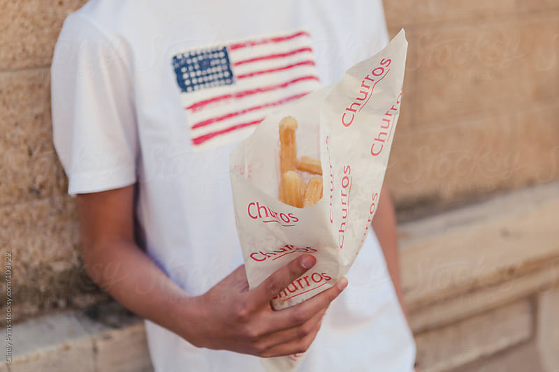 Hand of a boy holding a bag of churros and wearing a shirt with an American flag by Cindy Prins for Stocksy United