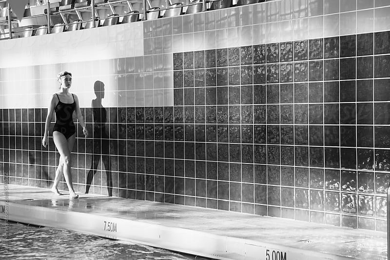 Young female swimmer walking alongside the skirting in pool by Danil Nevsky for Stocksy United