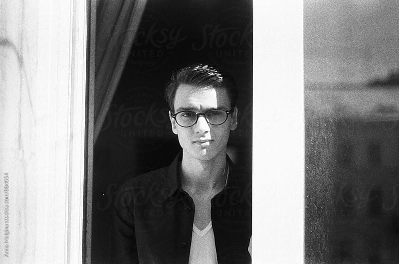 A black and white film portrait of a young beautiful man with eyeglasses by Anna Malgina for Stocksy United